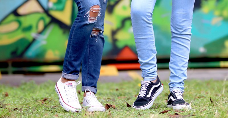 Young people's legs in jeans and trainers